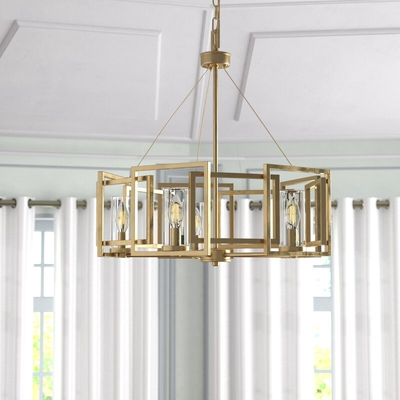 The round chandelier with square brass decorations around the outside
