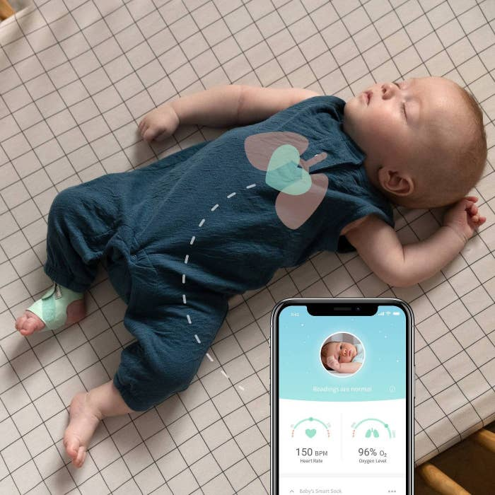 Sleeping baby wearing the sock next to a phone screen showing the baby's heart rate and oxygen level