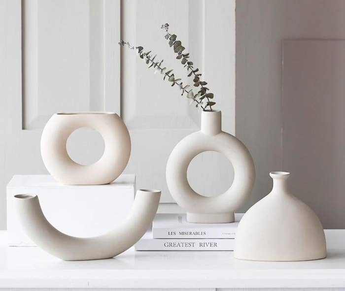 Four abstract vases in the shape of elbow macaroni, a half-cut jug, and two with holes in the center