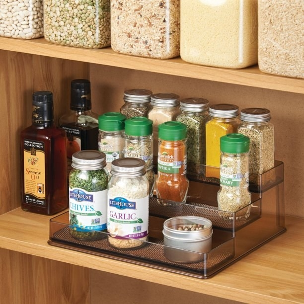 The 3-tier spice rack in a cabinet with spices on each tier