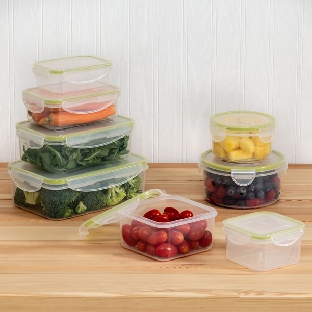 8 of the storage containers with various fruits and vegetables in them