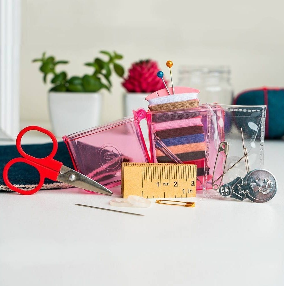 pink sewing kit with a ruler, scissors, buttons, and threads