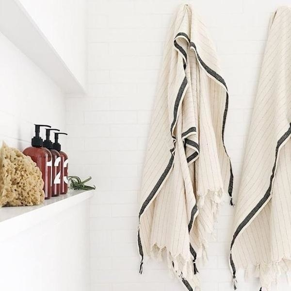 Two ivory bath towels with thing gray stripes, black side details, and fringed edges
