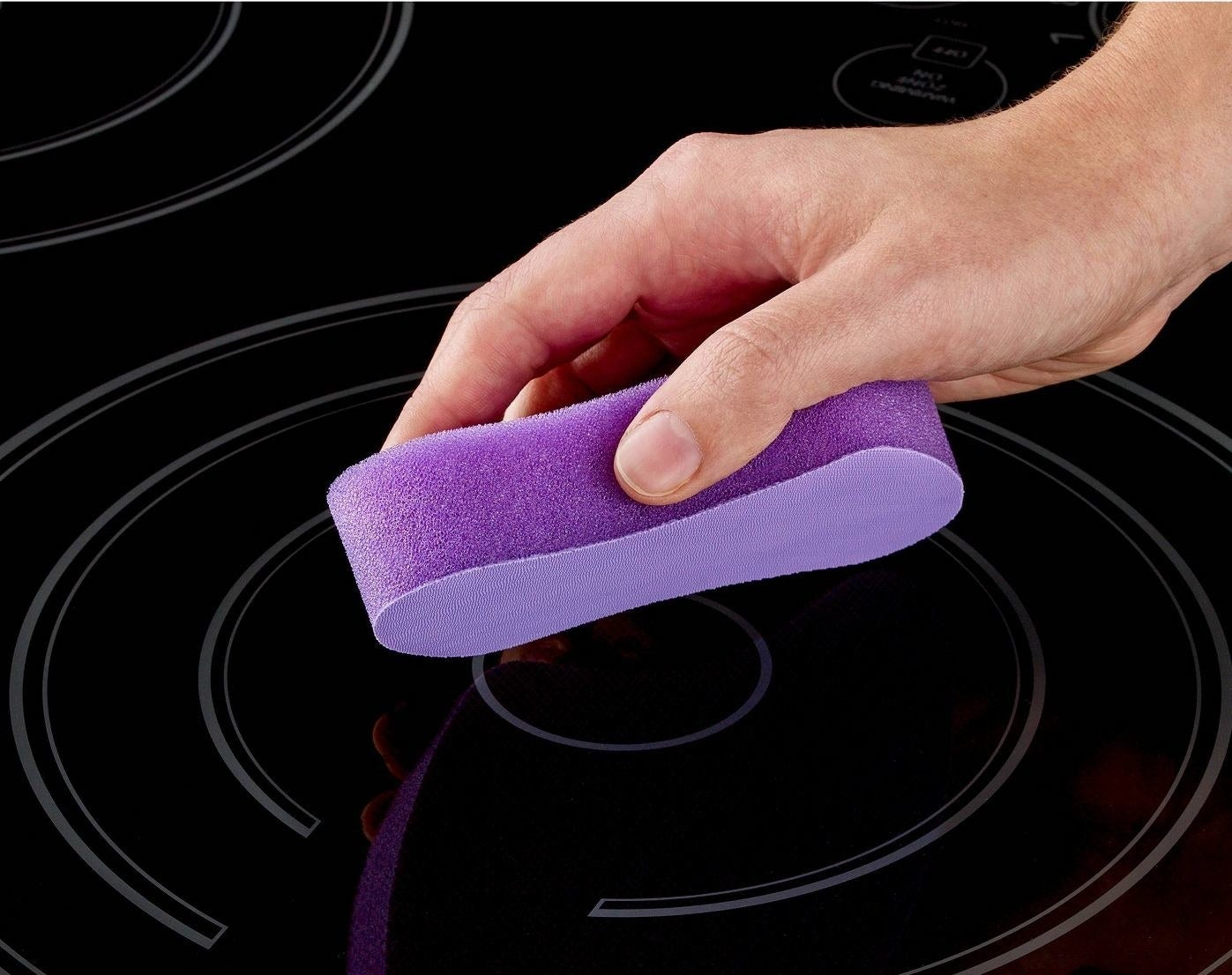 person using purple cleaning pad for a glass stovetop