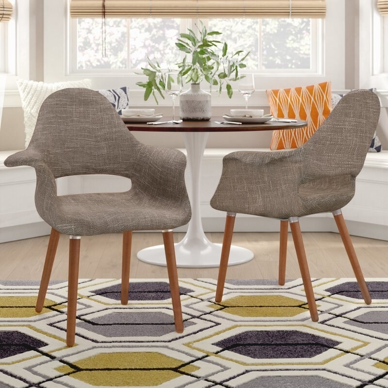Grey chairs with curved half-arms and wooden legs