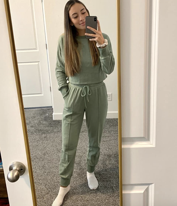 reviewer wearing olive green drawstring pants and matching sleeved crewneck sweater