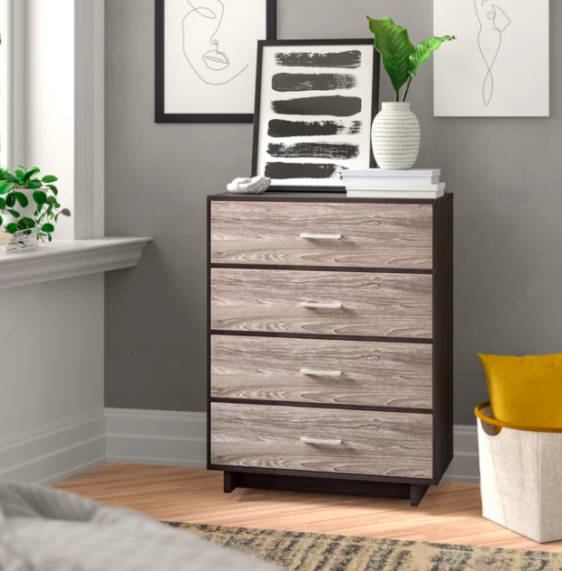 Light wood and black four-drawer dresser with a minimalist-inspired art print and white vase with plants on top