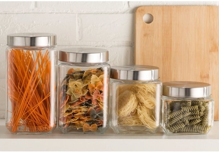 The Joss & Main Essentials 4 Piece Screw Top Glass Kitchen Canister Set being used to store different types of uncooked pasta