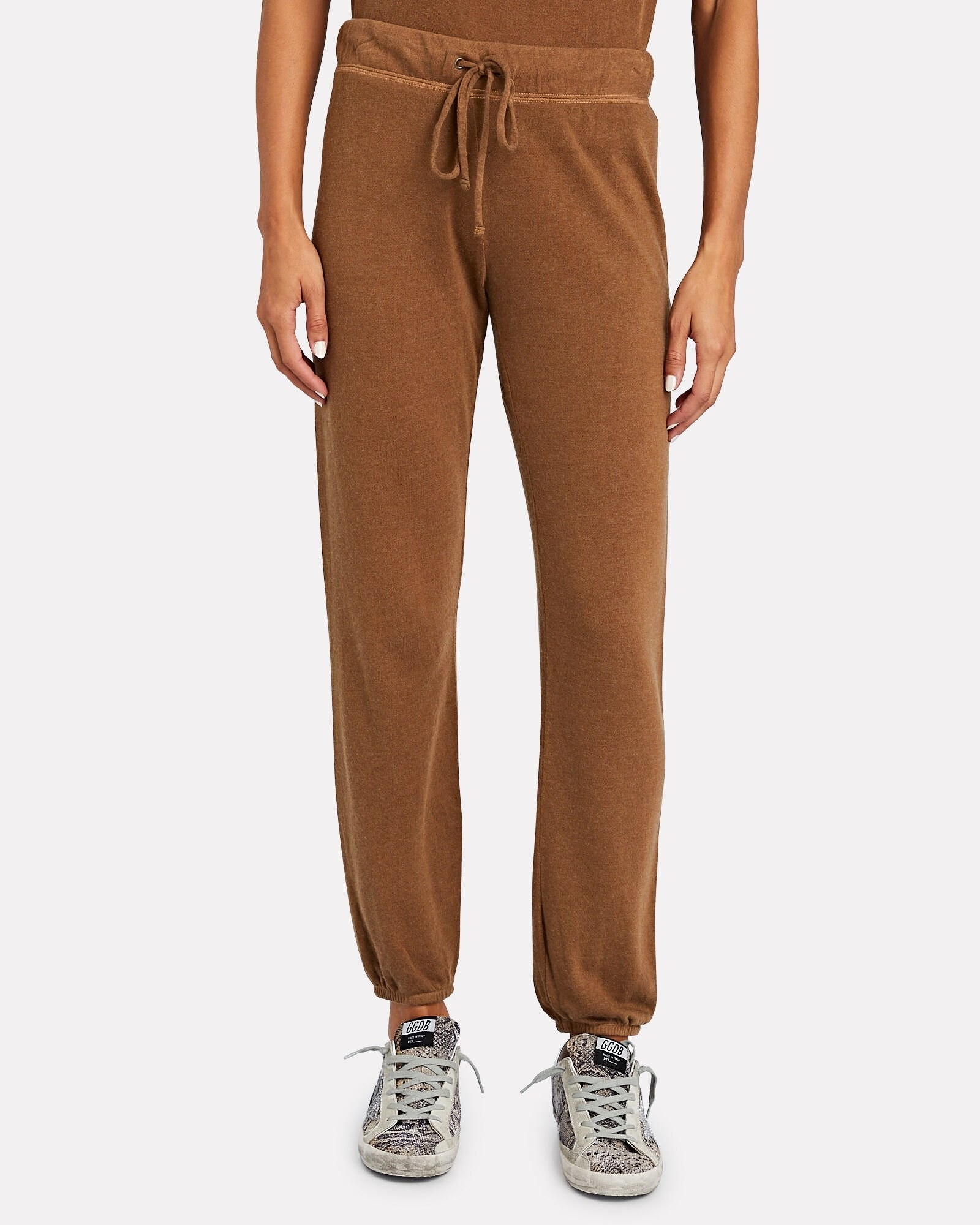 A model wearing the cognac colored joggers, which have a drawstring waist and are gathered at the ankles