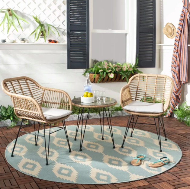 Two light beige wicker patio chairs and matching glass-top table on light blue, Ikat-print rug outside