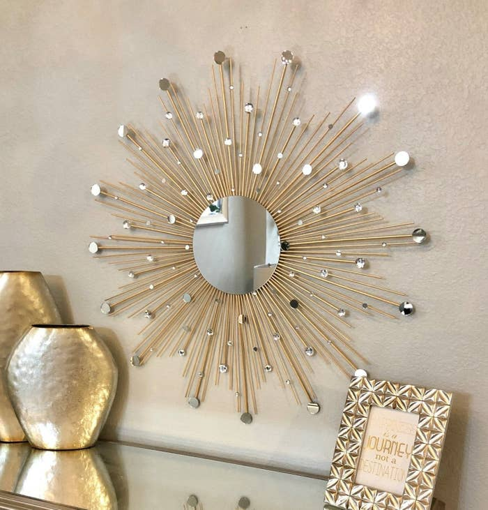 The circular mirror, which has gold spiky sun rays coming out of it and gems and small mirrors placed throughout the rays
