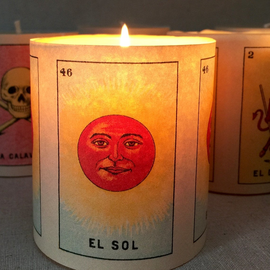 the candle with El Sol loteria card on candle jar