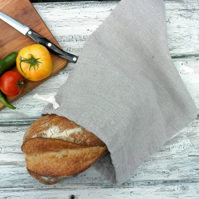 A loaf of bread in a gray linen drawstring bag