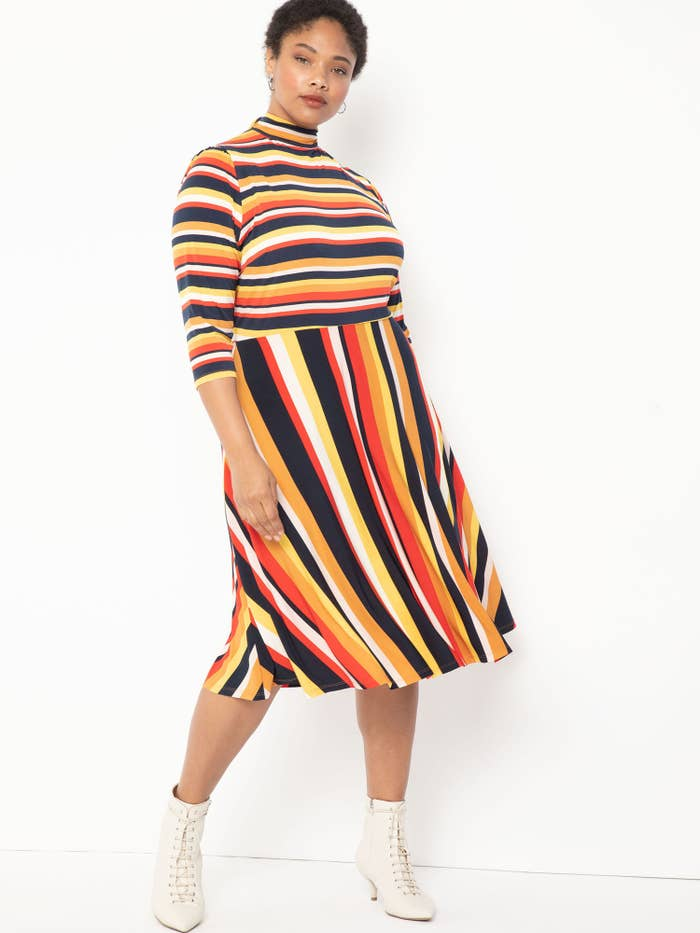 Model wearing plus-size striped knee-length dress with white boots