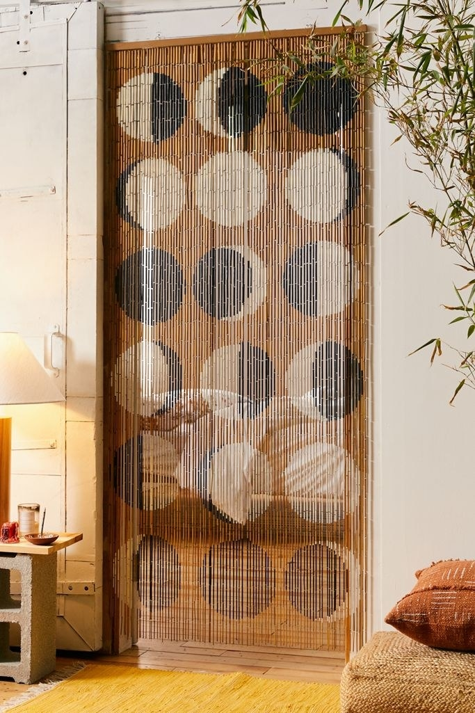 Beaded curtain with moon phase pattern dividing hallway from room