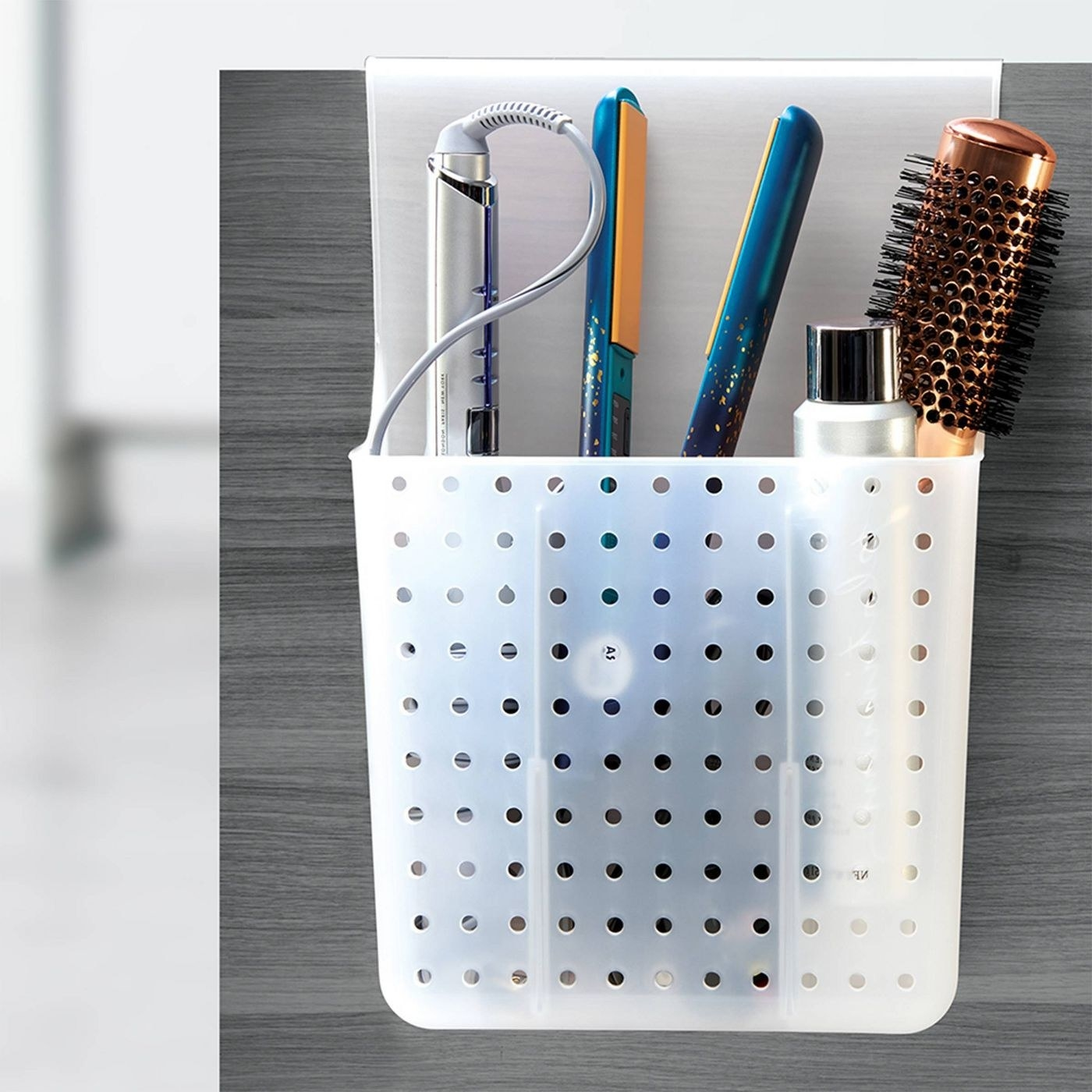 hair tool organizer on the back of a cabinet door with flat irons and brushes in them