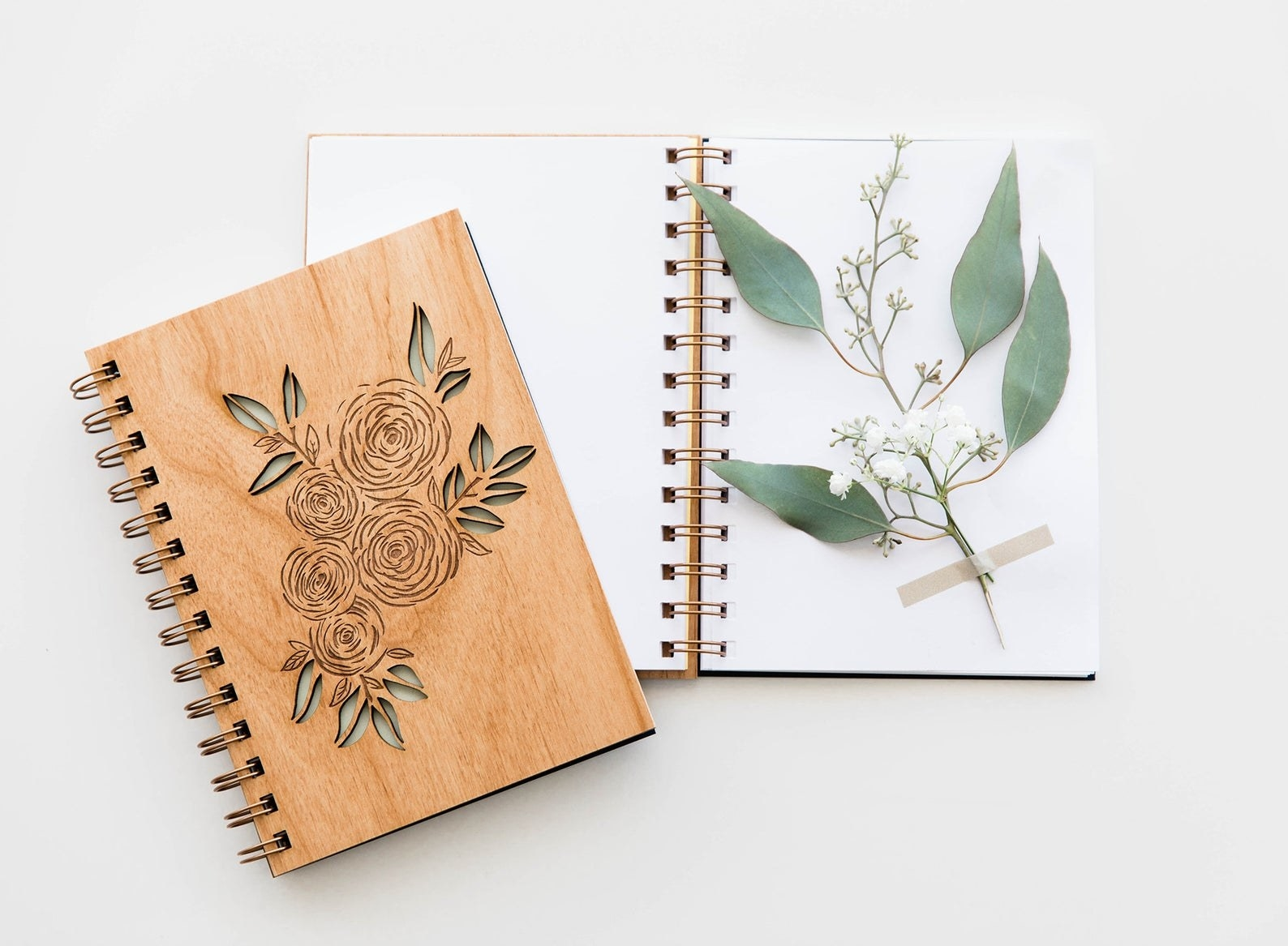 The spiral journal with a cover that's wooden and laser cut to look like roses with leaves