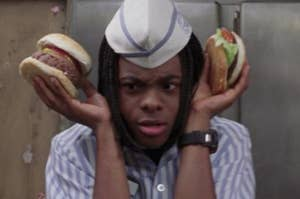 Kel from the movie Good Burger holding two burgers up to his ears