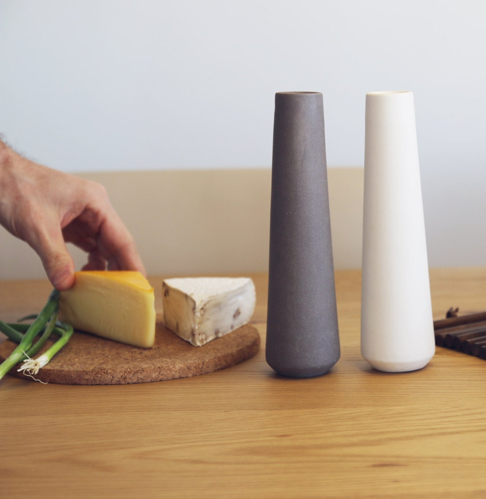 Two tall gray and white shakers on a table