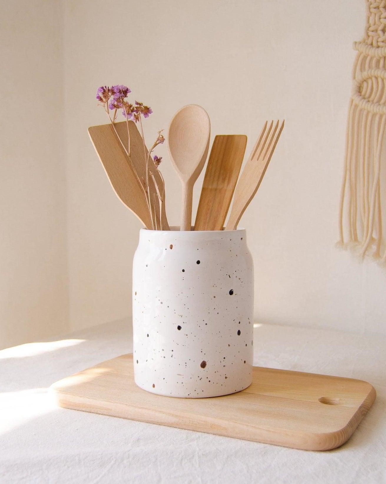 wooden utensils in a white speckled stoneware crock