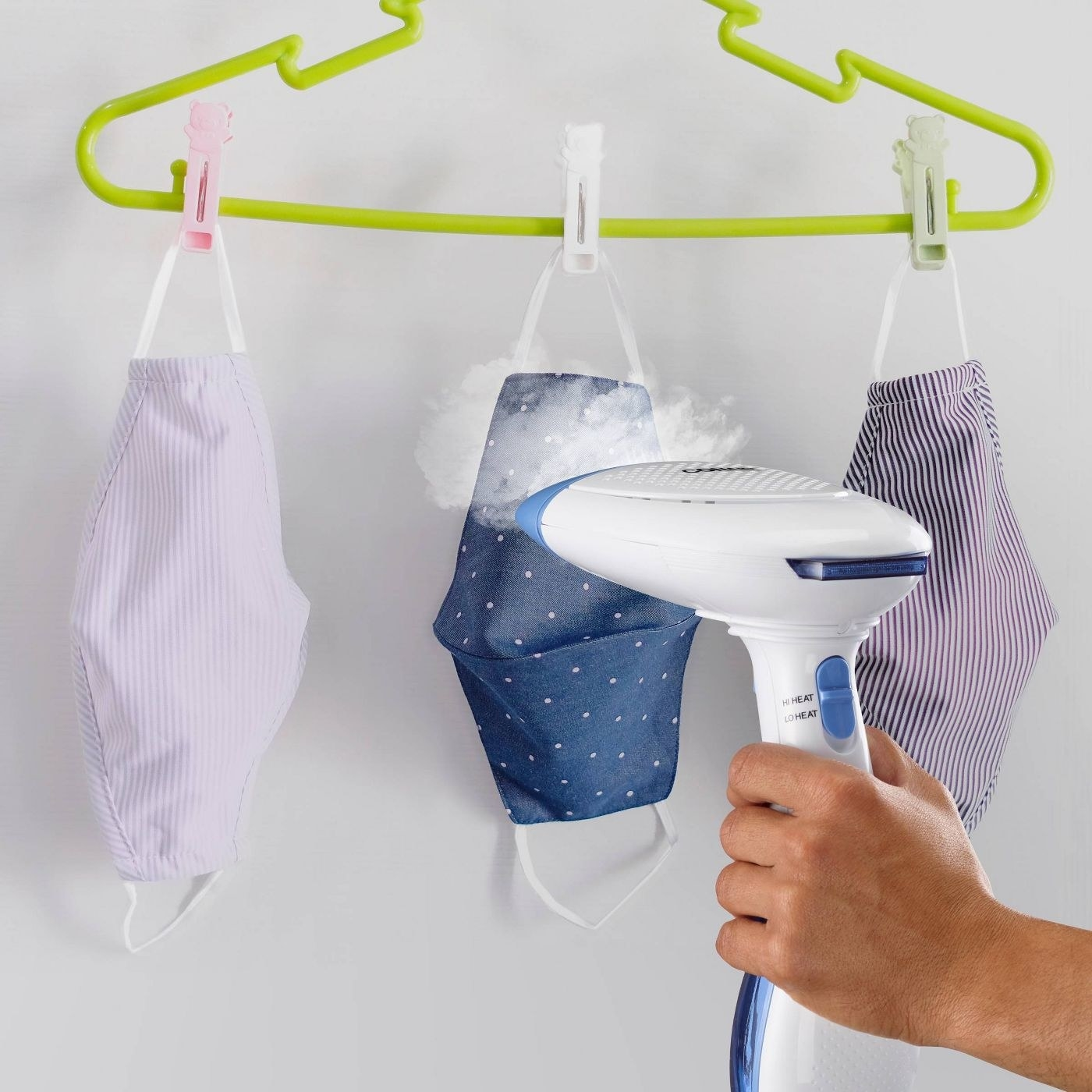 person using fabric steamer to dewrinkle a face mask