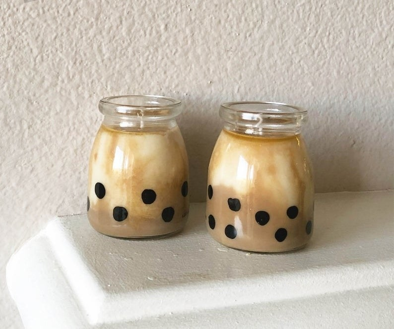Two tiny candle jars with the outside painted to look like boba pearls