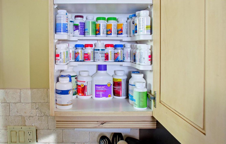 spice shelf organizer in a medicine cabinet organizing bottles of medicine