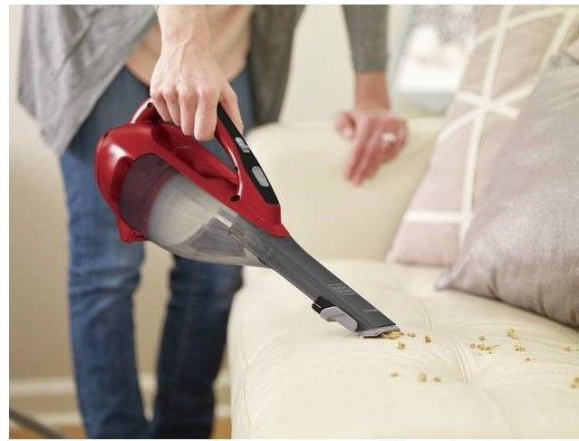 Perosn using the handheld vacuum to clean up crumbs on a couch