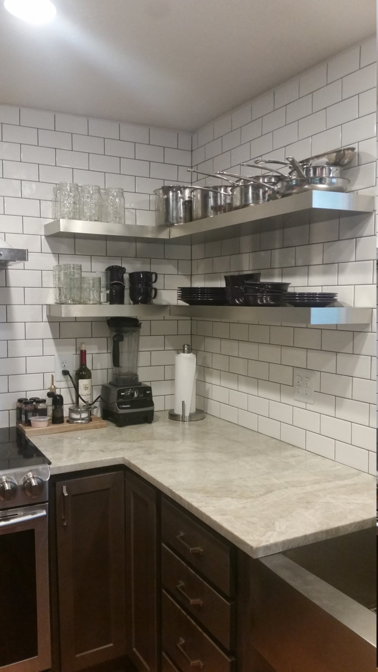 The shelves mounted on corner walls of a kitchen