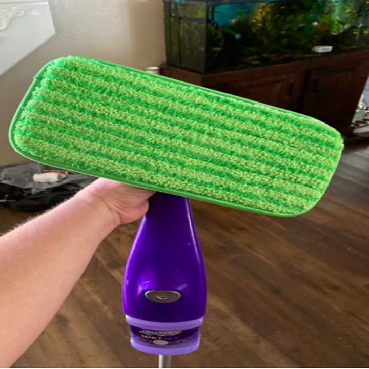 A reviewer holding up their Swiffer with the green pad on the bottom