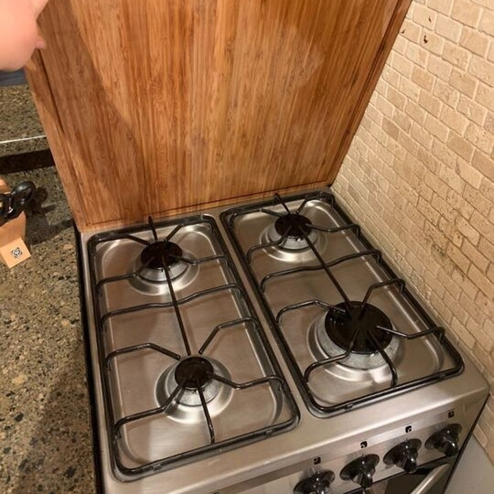 a hand lifting the cover showing the stove-top underneath
