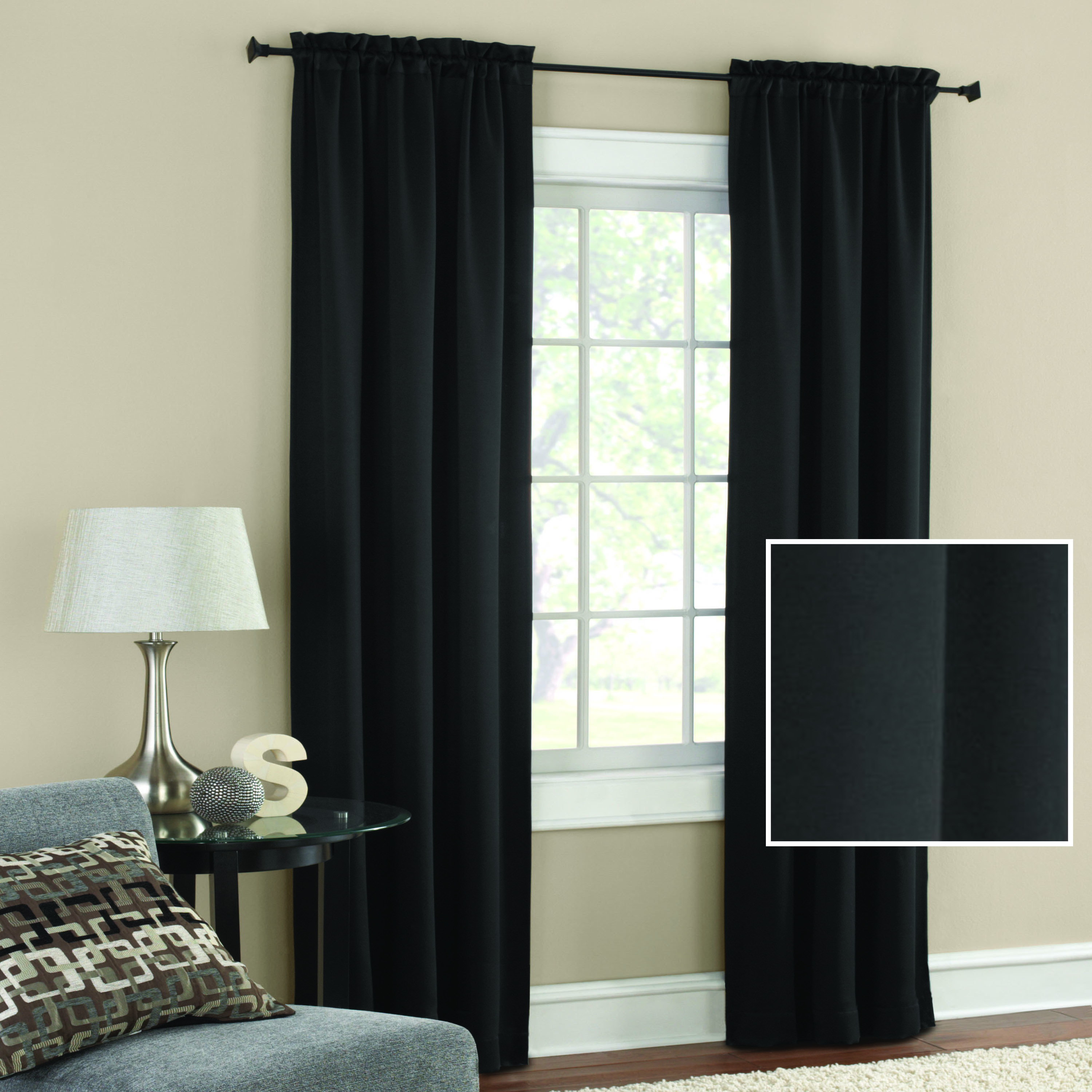 The black out curtains in black draped on a window