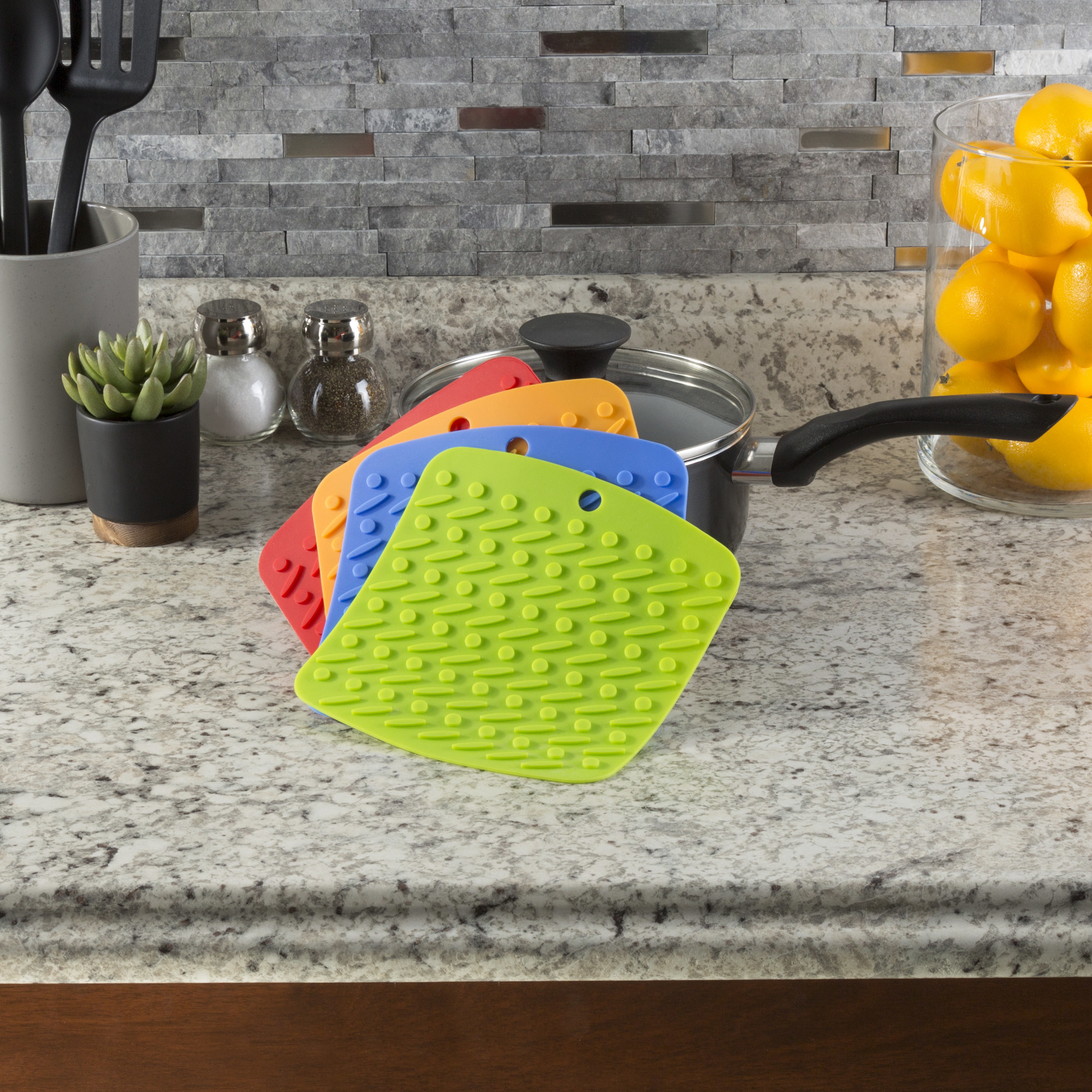 The 4 silicone pot holders on a kitchen counter