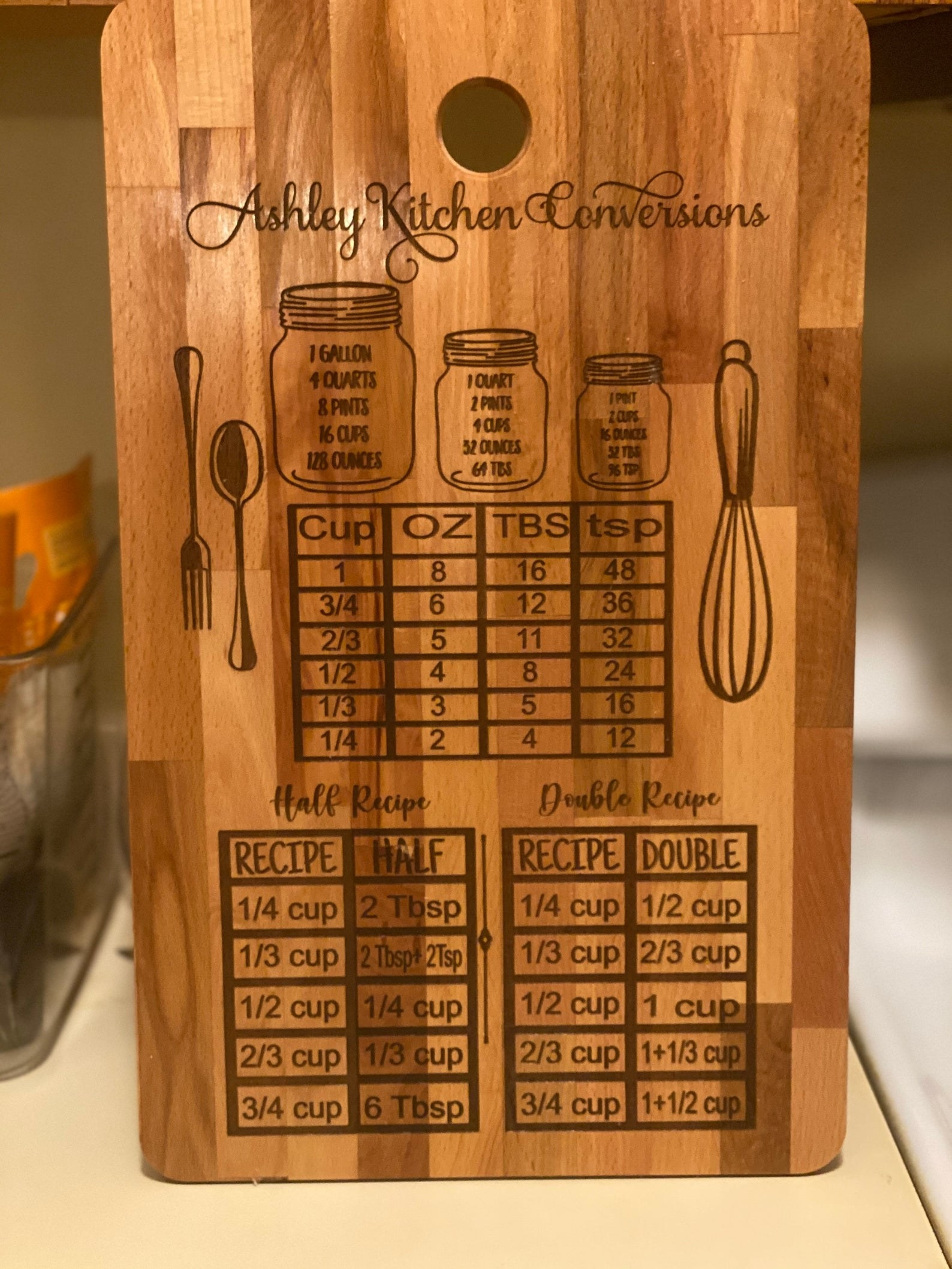 A wood cutting board depicting liquid measurements, cup, ounce, tablespoon, and teaspoon conversions, and instructions for halving and doubling recipes