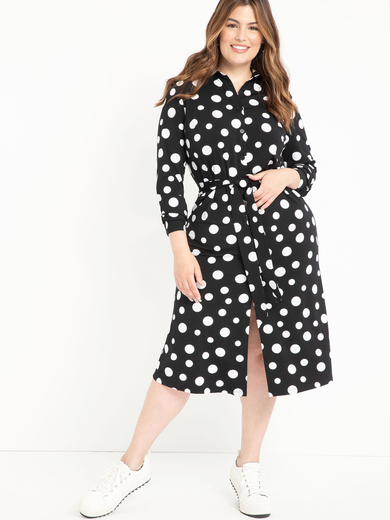 Model wearing black and white polka dot dress with white shoes