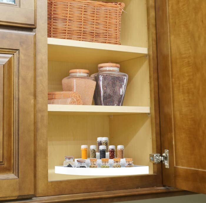 The organizer being used to hold spices in a cabinet