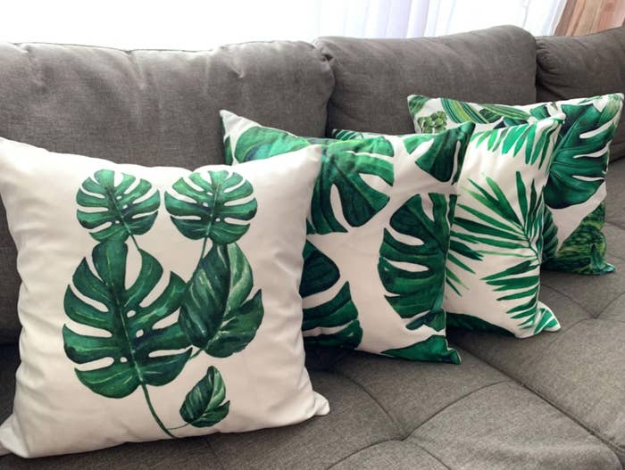 Four green leaf throw pillow covers lined up on a couch.