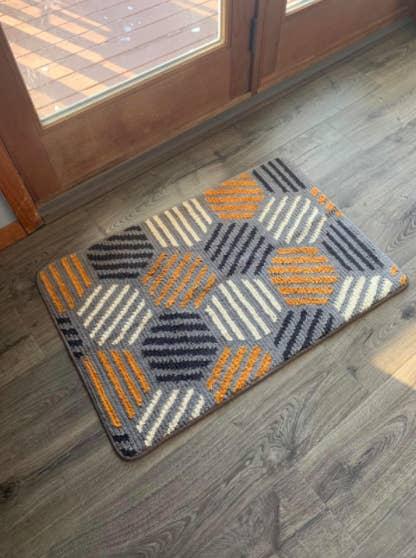Gray, white, dark blue, and yellow geometric-print door mat on a gray hardwood floor in front of a wood glass door