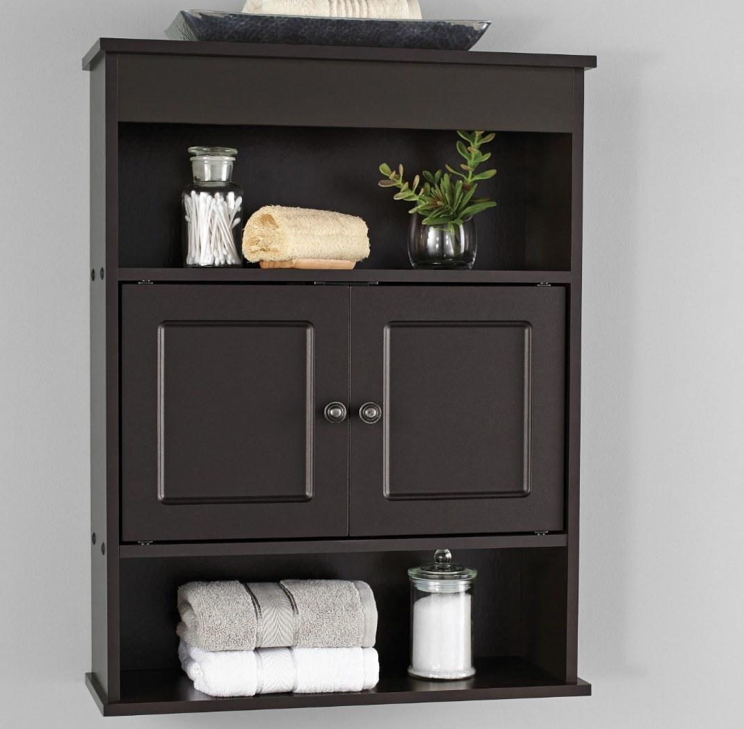 A bathroom cabinet holding towels, a loofa, and qtips