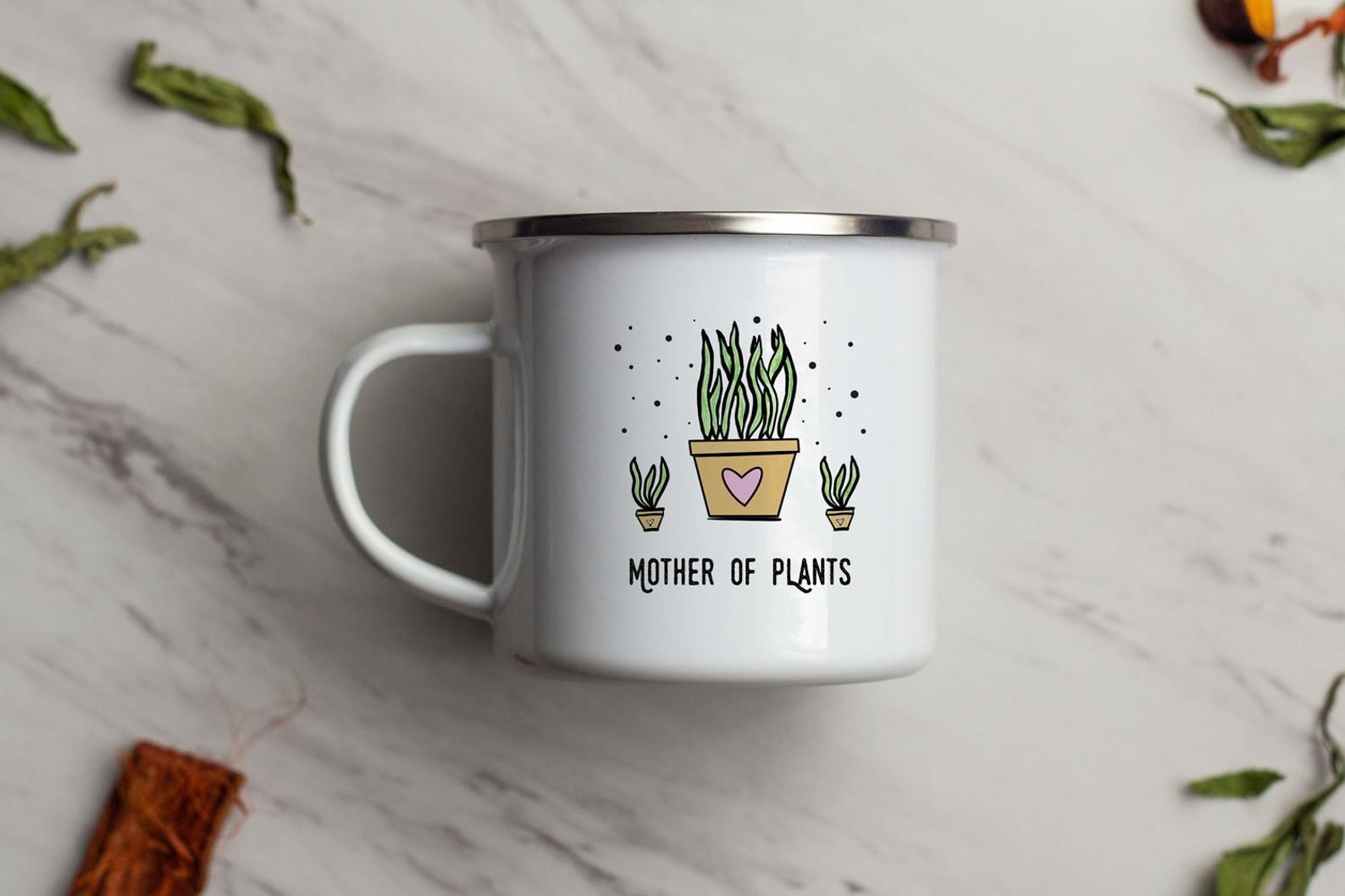 """Enamel mug with three plants and the words """"Mother of Plants"""""""