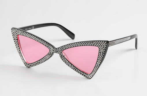 A pair of studded sunglasses resting on a simple background