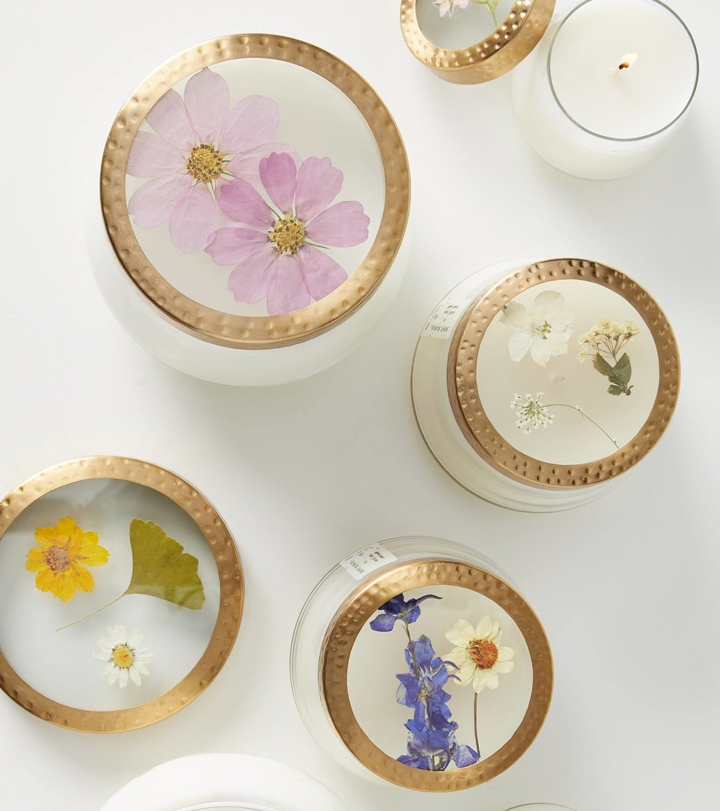 Candles of different sizes with various pressed flowers displayed on the lid