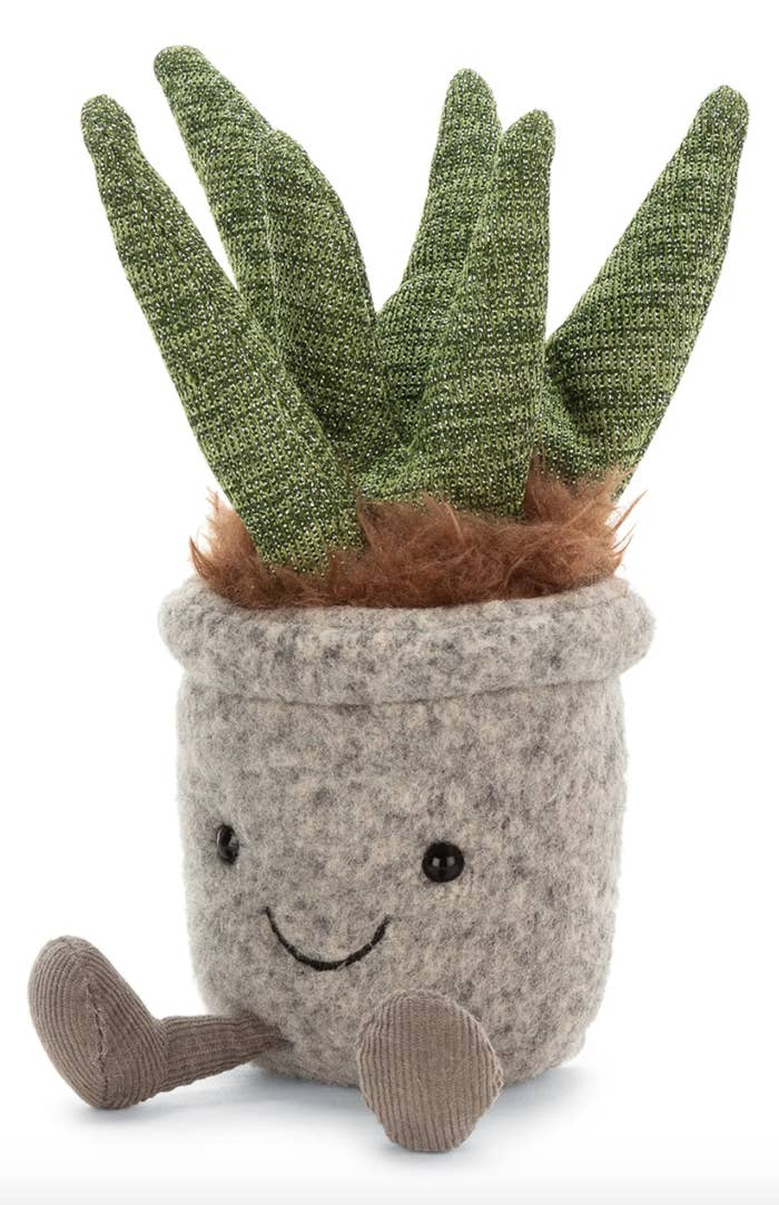 Stuffed toy Aloe plant with a smiling face and tiny legs.