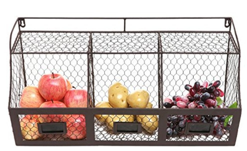 The storage basket being used to hold apples, potatoes, and grapes