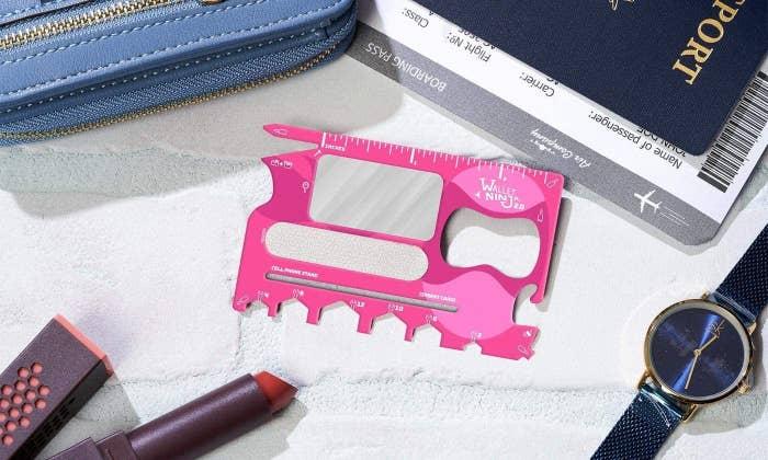 The rectangular multi tool arranged next to a watch, a lipstick, and a passport
