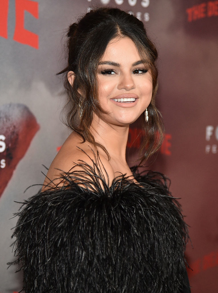 Selena smiling in a feathery dress