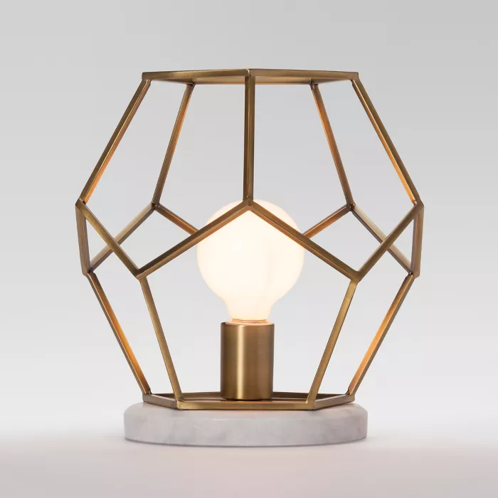 A geometric accent lamp with a cage-inspired brass design and a marble base