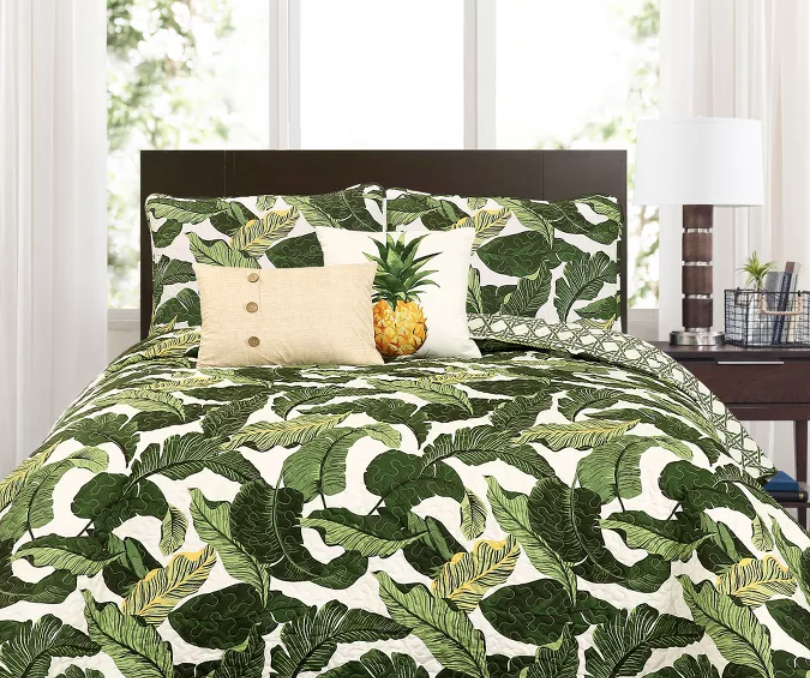 Dark green leaf patterned quilt with matching pillow shams, pineapple decorative pillow, and tan buttoned decorative pillow.