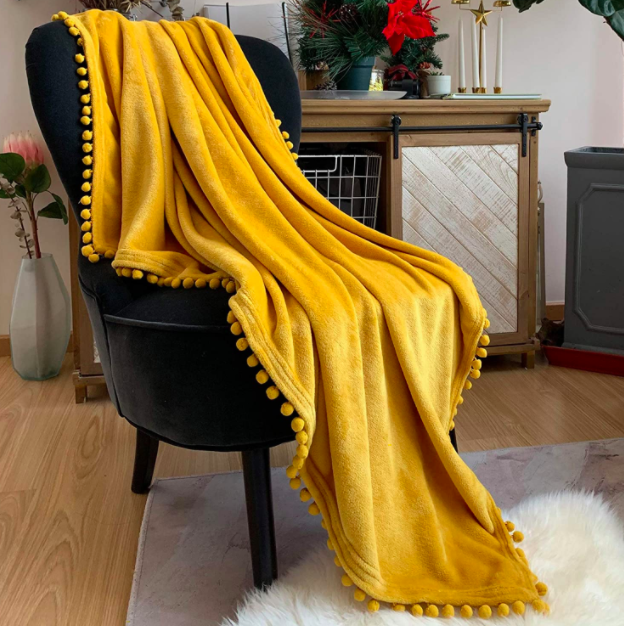 Yellow pompom throw blanket on top of a black velvet armchair in a living room