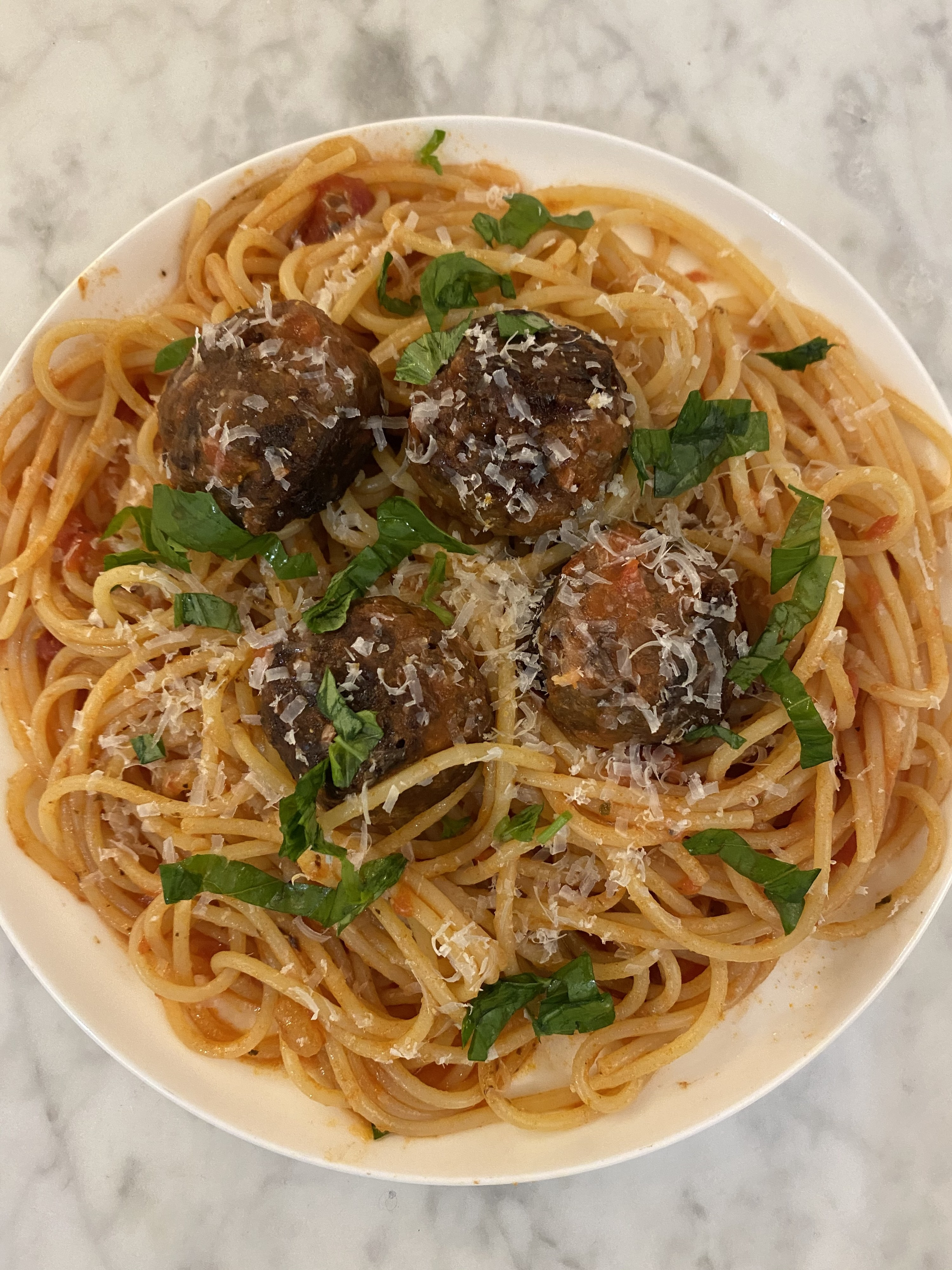 A plate of spaghetti with tomato sauce, basil, parmesan, and Beyond Meat meatballs on top.